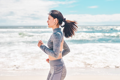 Buy stock photo Shot of a fit young woman going for a jog along the beach