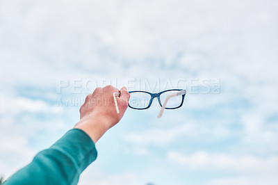 Buy stock photo Cropped shot of an unrecognizable boy holding his glasses up against the sky