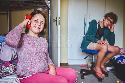 Buy stock photo Shot of a young girl and her older brother bonding at home