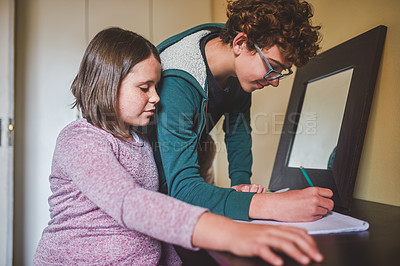 Buy stock photo Cropped shot of a boy helping his younger sister with her homework
