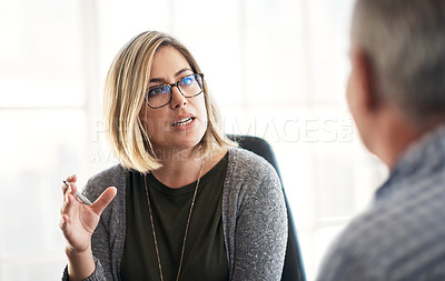 Buy stock photo Shot of a young businesswoman having a discussion with her colleague in a modern office