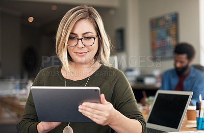 Buy stock photo Shot of a young businesswoman using a digital tablet in a modern office