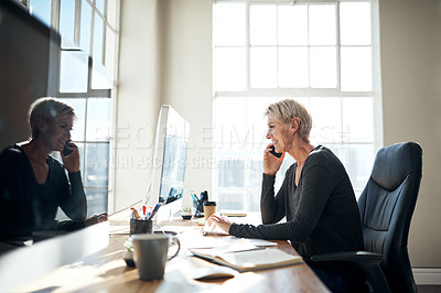 Buy stock photo Shot of a mature businesswoman talking on a cellphone while working on a computer in an office