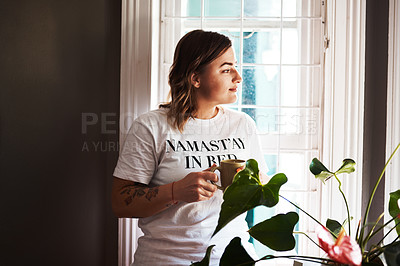 Buy stock photo Cropped shot of a beautiful young woman having coffee at home