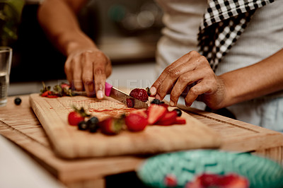 Buy stock photo Cropped shot of a woman making a healthy snack with strawberries at home