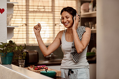 Buy stock photo Shot of a young woman making a healthy snack with strawberries and listening to music at home