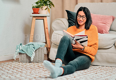 Buy stock photo Shot of a young woman relaxing on the floor in the living room and reading a book at home