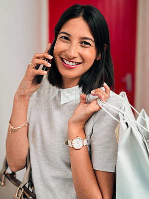Buy stock photo Shot of a young woman using a smartphone while spending a day shopping