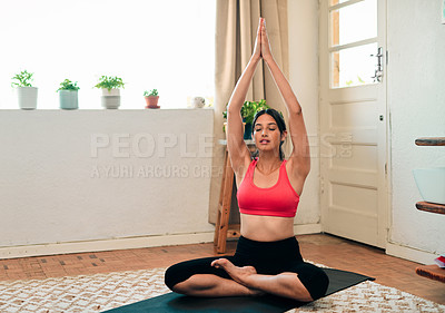 Buy stock photo Shot of an attractive young woman doing yoga at home