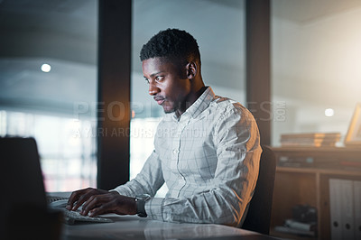 Buy stock photo Cropped shot of a handsome young businessman sitting alone and typing on his keyboard in his office at night