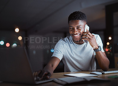 Buy stock photo Cropped shot of a handsome young businessman making a phonecall while working on his laptop late at night in the office