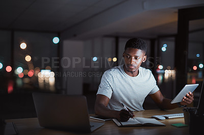 Buy stock photo Cropped shot of a handsome young businessman making notes while working on his tablet late at night in the office