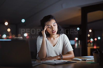 Buy stock photo Cropped shot of an attractive young businesswoman suffering with a headache while working late at night in her office