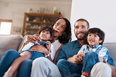 Buy stock photo Cropped shot of a family of four sitting together on the sofa at home
