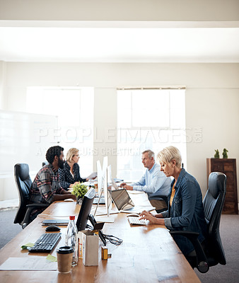 Buy stock photo Cropped shot of a creative mature businesswoman working in an office with her colleagues in the background