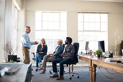 Buy stock photo Full length shot of a mature businessman presenting and pitching ideas to his colleagues inside an office
