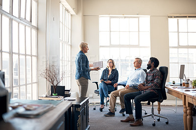 Buy stock photo Full length shot of a mature creative businesswoman presenting and pitching ideas to her colleagues inside an office