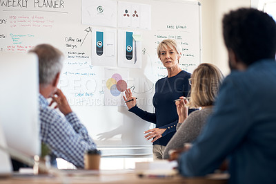 Buy stock photo Cropped shot of a mature businesswoman presenting and pitching ideas to her colleagues inside an office