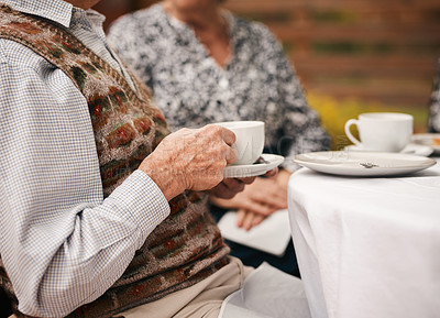 Buy stock photo Cropped shot of an unrecognizable man sitting and enjoying a cup of tea during a birthday party outdoors