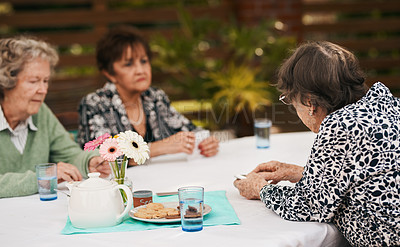 Buy stock photo Cropped shot of a group of senior people sitting together and playing a game of bridge during a tea party