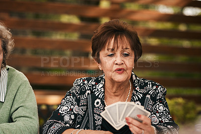 Buy stock photo Cropped shot of a senior woman sitting and playing a game of bridge with her friends during a tea party