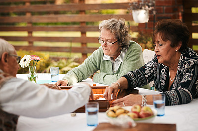 Buy stock photo Cropped shot of a group of senior people sitting together and playing a game of mahjong during a tea party