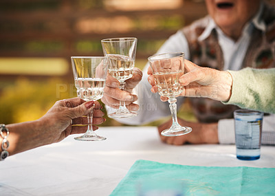 Buy stock photo Cropped shot of an unrecognizable group of seniors sitting and raising wine glasses for a toast during a birthday party