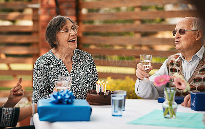 Buy stock photo Cropped shot of a happy senior couple sitting together and enjoying a glass of wine during a birthday party outdoors