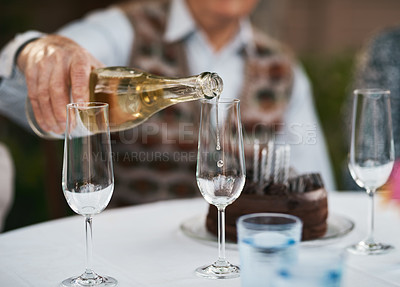 Buy stock photo Cropped shot of an unrecognizable senior man sitting and pouring champagne into glasses for a toast during a birthday party