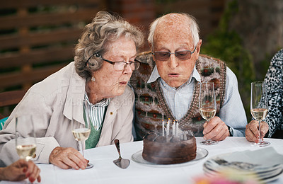 Buy stock photo Cropped shot of a senior couple sitting together and blowing out candles during a birthday party