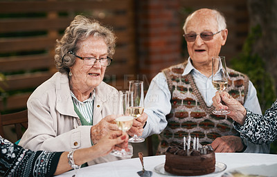 Buy stock photo Cropped shot of a group of seniors sitting together and toasting a glass of champagne during a birthday party outdoors
