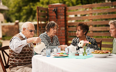 Buy stock photo Cropped shot of a happy group of senior people sitting together and enjoying a tea party outdoors