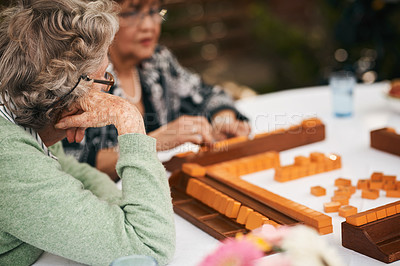 Buy stock photo Cropped shot of an unrecognizable group of seniors sitting and playing a game of mahjong during a tea party