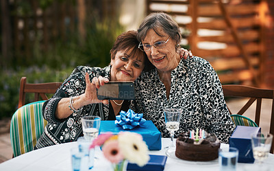 Buy stock photo Cropped shot of two senior women sitting together and taking a selfie with a cellphone during a tea party