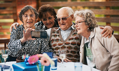 Buy stock photo Cropped shot of a group of senior people sitting and taking a selfie with a cellphone during a tea party