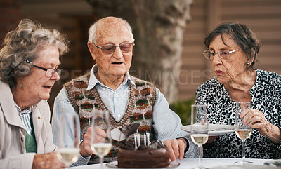 Buy stock photo Cropped shot of a group of senior people sitting and cutting a chocolate cake during a birthday party outdoors
