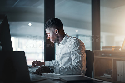 Buy stock photo Cropped shot of a handsome young businessman sitting alone in his office and reading paperwork at night