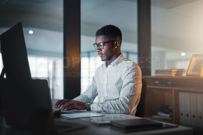 Buy stock photo Cropped shot of a handsome young businessman sitting alone in his office and using his computer during a late shift
