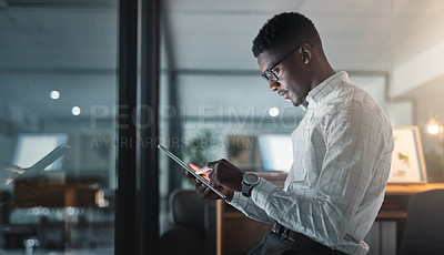 Buy stock photo Cropped shot of a handsome young businessman sitting alone in his office and using a tablet during a late shift