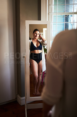 Buy stock photo Cropped shot of an attractive young woman admiring herself in the mirror in her bedroom at home