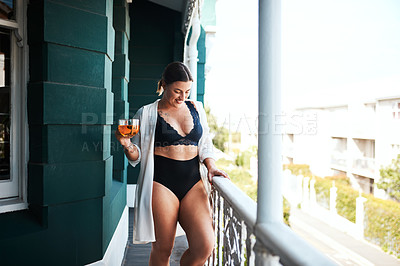 Buy stock photo Cropped shot of an attractive young woman smiling while holding a glass of tea on her balcony in the morning