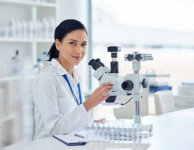 Buy stock photo Portrait of a young scientist using a microscope in a laboratory