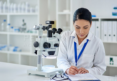 Buy stock photo Shot of a young woman filling out paperwork while working a laboratory