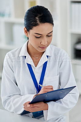 Buy stock photo Shot of a confident young woman filling out paperwork while working in a laboratory