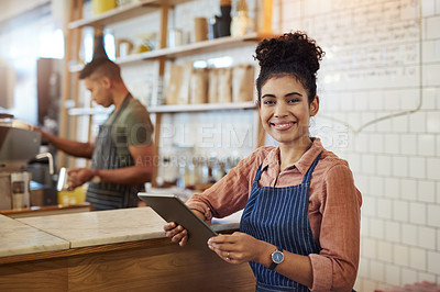 Buy stock photo Portrait of a young woman using a digital tablet while working in a cafe with her colleague in the background
