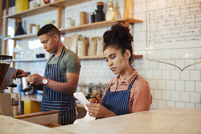 Buy stock photo Shot of a young woman going through receipts while working in a cafe with her colleague in the background