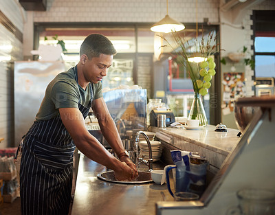 Buy stock photo Shot of a young man washing his hands at a basin in a cafe