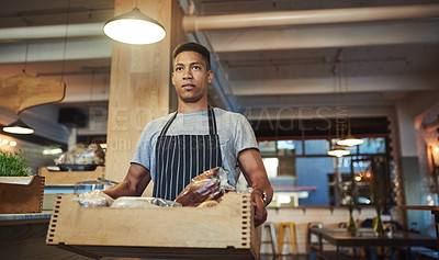 Buy stock photo Shot of a young man carrying a crate while working in a cafe