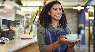 Buy stock photo Shot of a young waitress holding a cup of coffee in a cafe