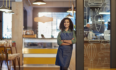 Buy stock photo Portrait of a young woman standing in the doorway of a cafe